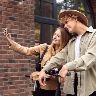 Pareja tomando selfie al aire libre con scooters eléctricos