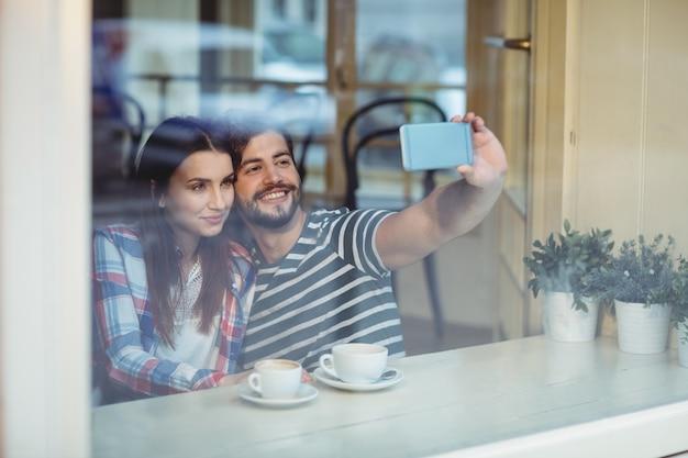 Pareja tomando selfie en café