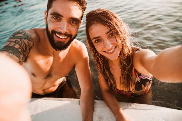 Pareja tomando selfie en el mar con tabla de surf