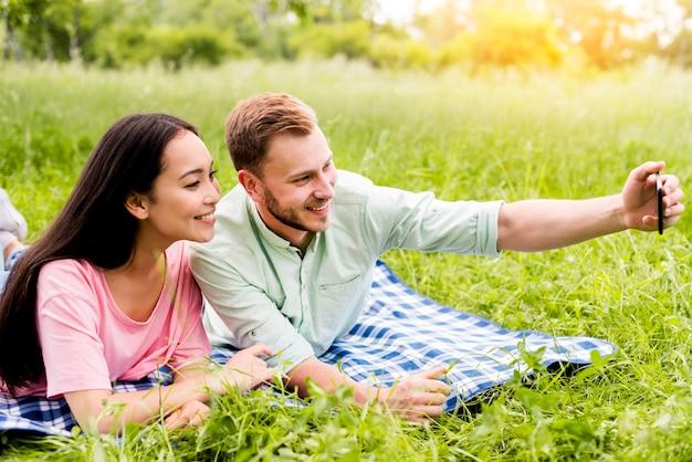 Pareja tomando selfie en picnic