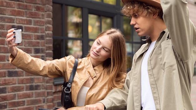 Pareja tomando selfie con scooters fuera