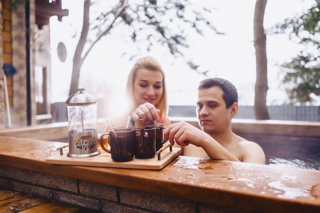 Pareja tomando té caliente mientras está sentada en el invierno afuera del spa caliente