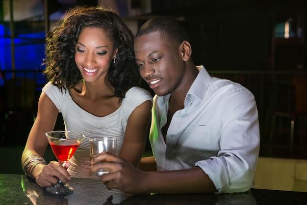 Pareja tomando unos tragos en la barra de bar en el bar