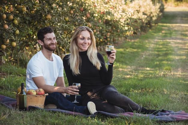 Pareja tomando vino en huerto de manzanas