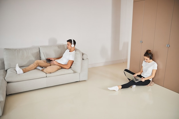 Pareja trabajadora con ordenadores portátiles para trabajar desde casa