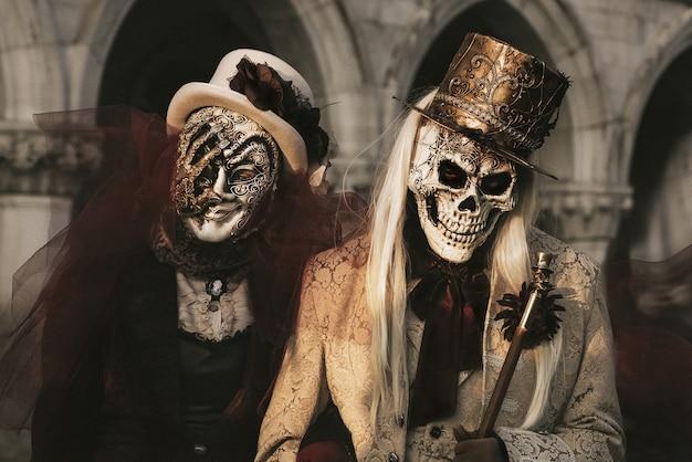 Pareja en trajes de esqueleto en el carnaval de venecia. celebración de halloween