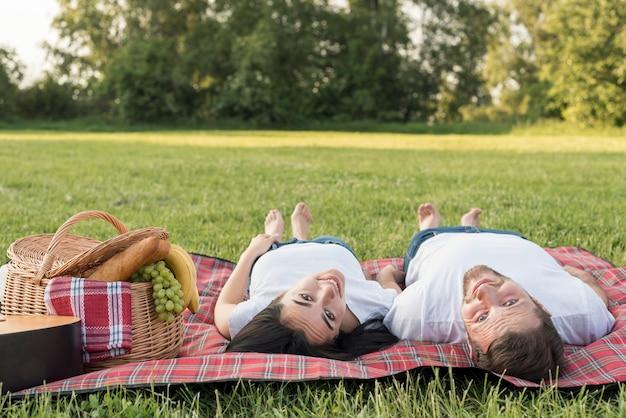 Pareja tumbada sobre manta de picnic