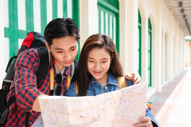 Pareja de turistas asiáticos buscando dirección en el mapa en bangkok, tailandia