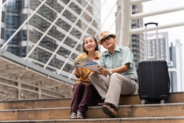 Una pareja de turistas asiáticos mayores que visitan la capital felices y se divierten y miran el mapa para encontrar lugares para visitar.
