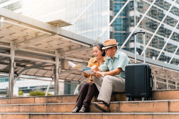 Una pareja de turistas asiáticos mayores que visitan la capital felices y divirtiéndose