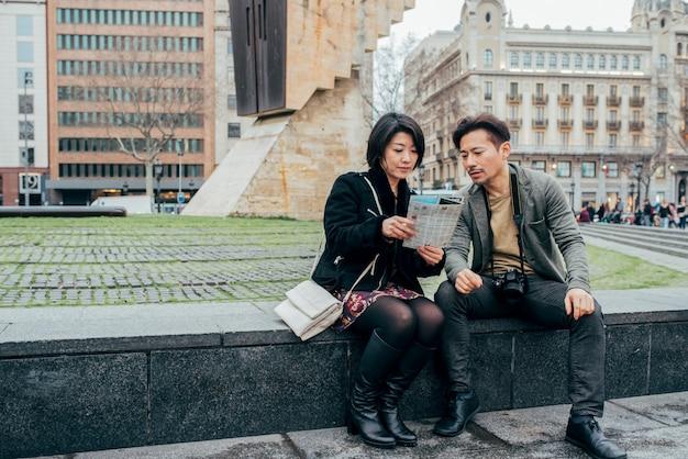 Pareja de turistas asiáticos mirando la tableta