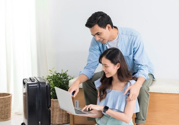 Pareja de turistas asiáticos planificando información de viaje con una computadora portátil y empacando maletas para viajar antes de la fecha de viaje en el fondo de casa.