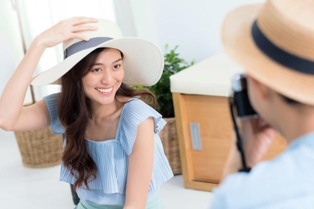 Pareja de turistas asiáticos que planifican información de viaje y toman fotos para viajar antes de la fecha de viaje en el fondo de casa.