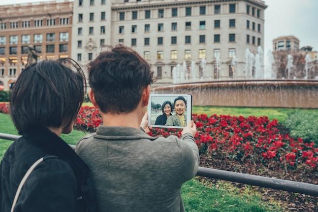 Pareja de turistas asiáticos tomando un selfie en la tableta