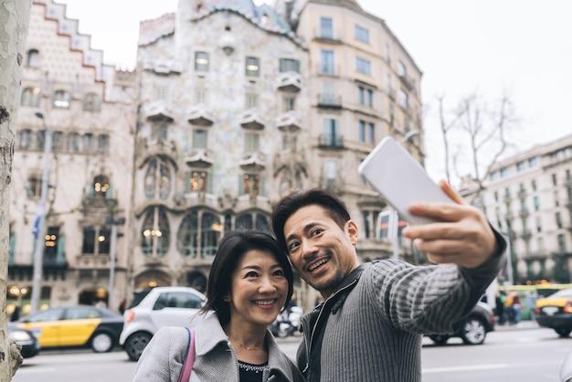 Pareja de turistas asiáticos tomando una selfie con un teléfono móvil