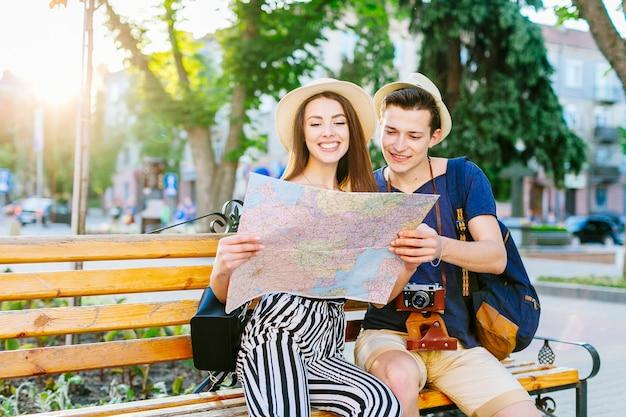 Pareja de turistas en banco mirando a mapa