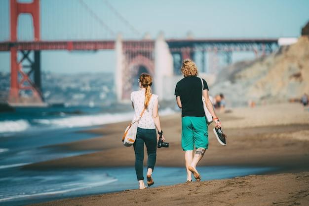 Pareja de turistas caminando por la playa con cámara