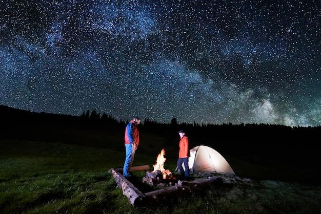 Pareja de turistas cerca de fogatas y carpas bajo el cielo nocturno lleno de estrellas y vía láctea