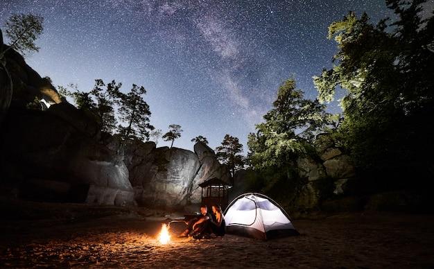 Pareja de turistas descansando junto al campamento, carpa de fogata en la noche