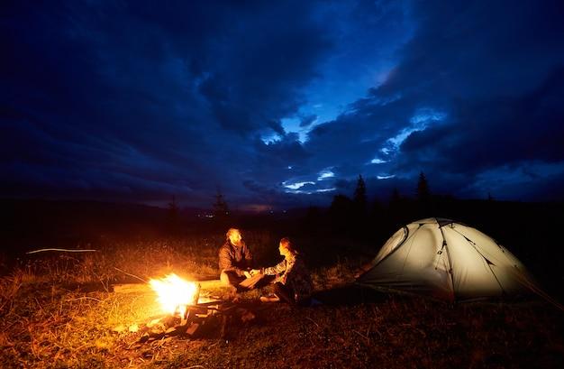 Pareja de turistas descansando por la noche acampando