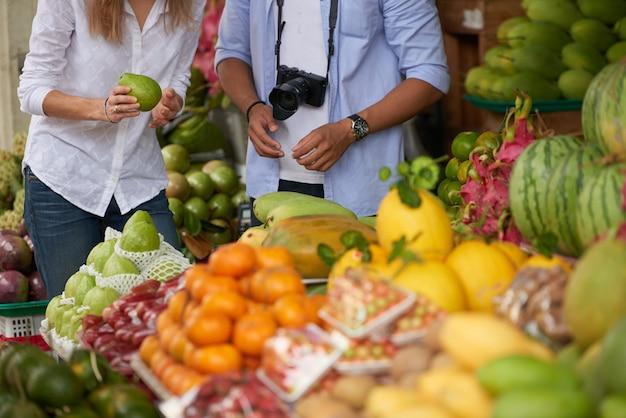 Pareja de turistas eligiendo frutas