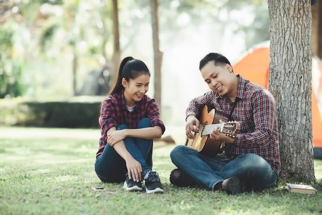 Pareja de turistas enamorados de tocar la guitarra en la naturaleza