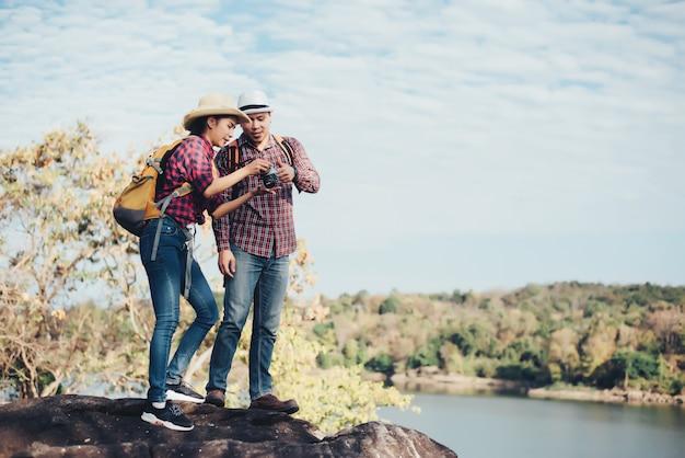 Pareja de turistas con fotografía en montaña.