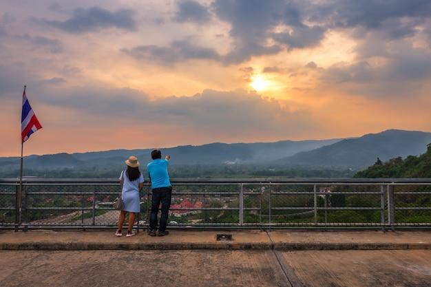 Pareja de turistas con una gran vista a la vista del río y las montañas en la presa khun dan prakan chon