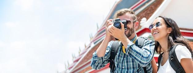 Pareja de turistas interraciales que toman fotos durante un viaje de vacaciones de verano en bangkok, tailandia