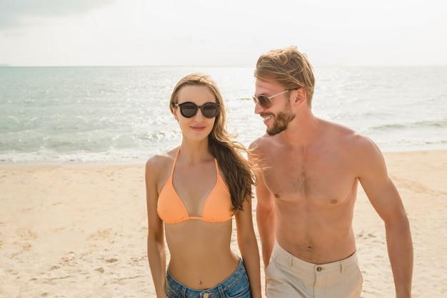 Pareja de turistas jóvenes caminando en la playa en verano