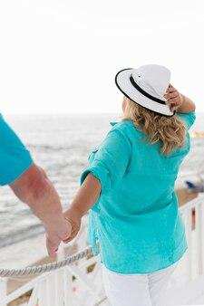 Pareja de turistas mayores tomados de la mano en la playa