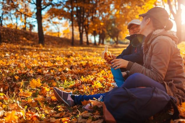 Pareja de turistas con mochilas que descansan en el bosque de otoño