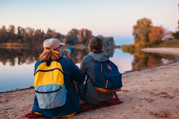 Pareja de turistas con mochilas que se relajan en la orilla del río otoño bebiendo agua y descansando