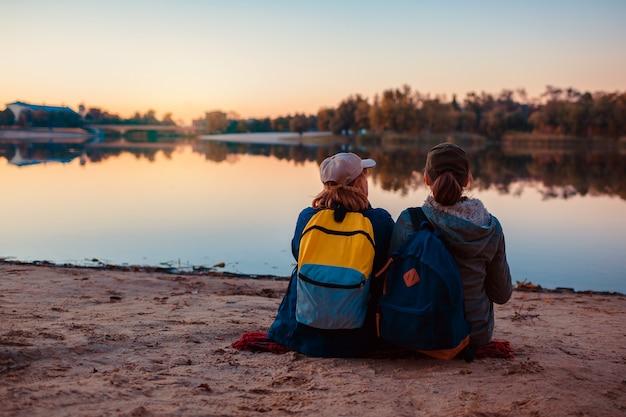 Pareja de turistas con mochilas relajantes por la orilla del río otoño