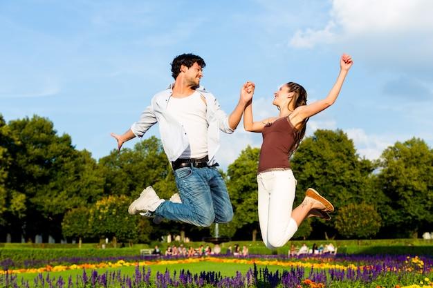 Pareja de turistas en parque de la ciudad saltando en sol