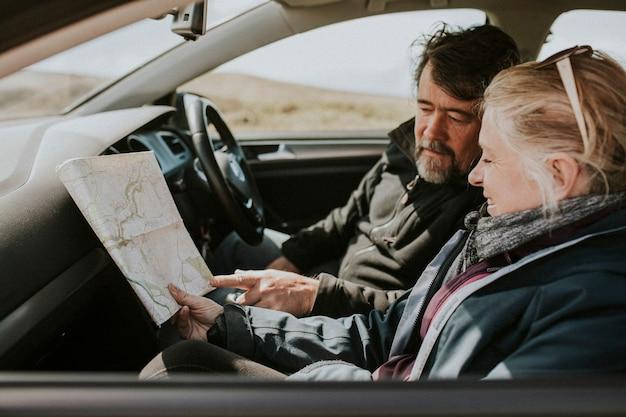 Pareja de turistas senior mirando el mapa en el coche