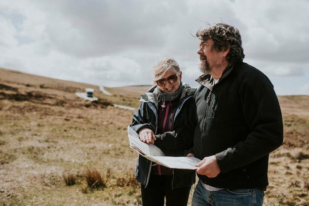 Pareja de turistas senior mirando el mapa mientras se pierde en gales, reino unido