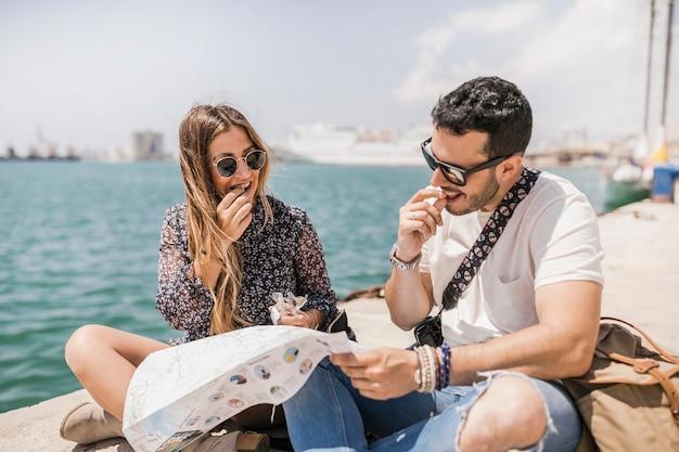 Pareja de turistas sentados cerca de la costa mirando el mapa para la dirección