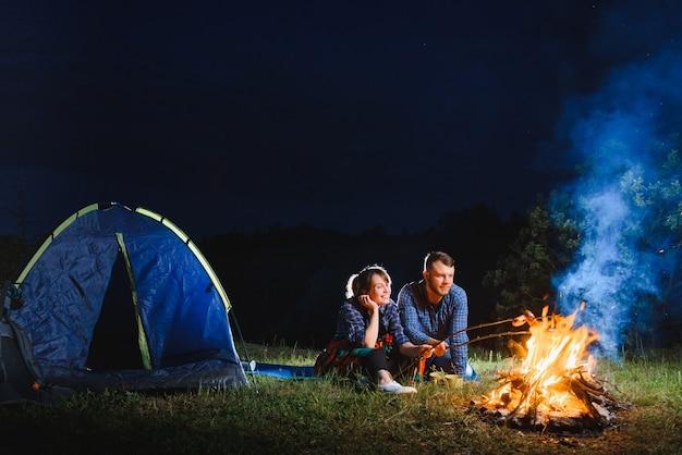 Pareja de turistas sentados frente a la carpa iluminada iluminada por una fogata ardiente