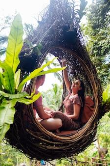 Una pareja de turistas sentados en un gran nido de pájaro en un árbol en la isla de bali