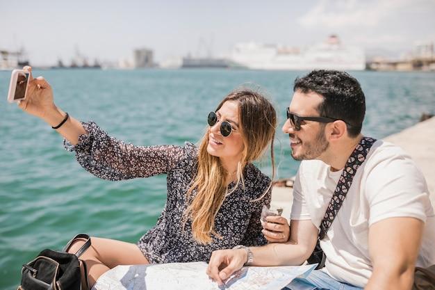 Pareja de turistas sentados con el mapa en el embarcadero tomando selfie en el teléfono celular