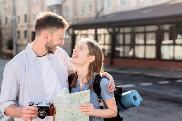 Pareja de turistas sonrientes al aire libre con mapa y cámara