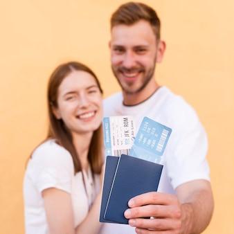 Pareja de turistas sonrientes mostrando pasajes aéreos y pasaportes