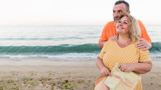 Pareja de turistas sonrientes posando en la playa