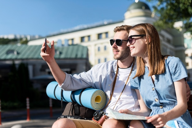 Pareja de turistas tomando selfie al aire libre