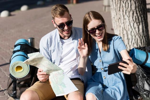 Pareja de turistas tomando una selfie con mapa