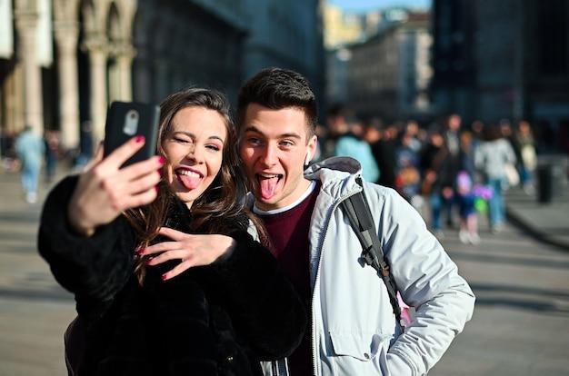 Pareja de turistas tomando selfies divertidos en milán