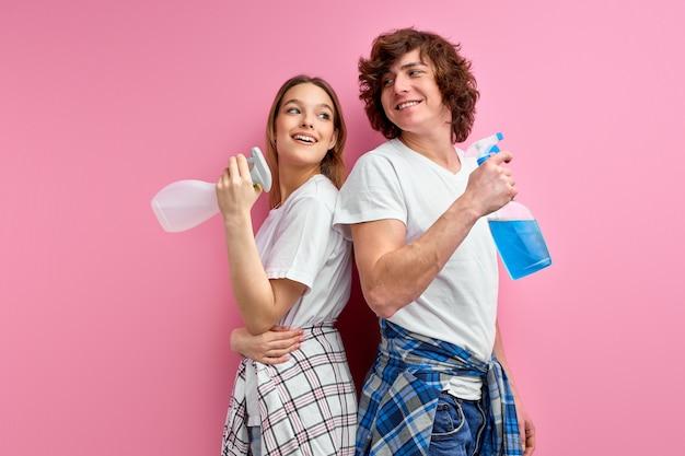 Pareja usa detergentes para limpiar aislados sobre fondo rosa de estudio.