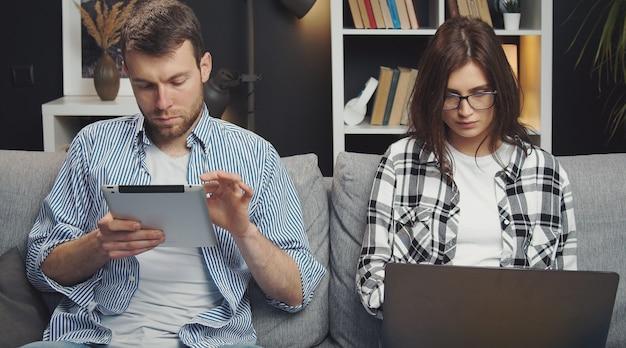 Pareja usando gadgets, mujer navegando por internet en la computadora portátil mientras su prometido lee desde la tableta, vista frontal