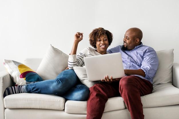 Pareja usando laptop juntos en el sofá